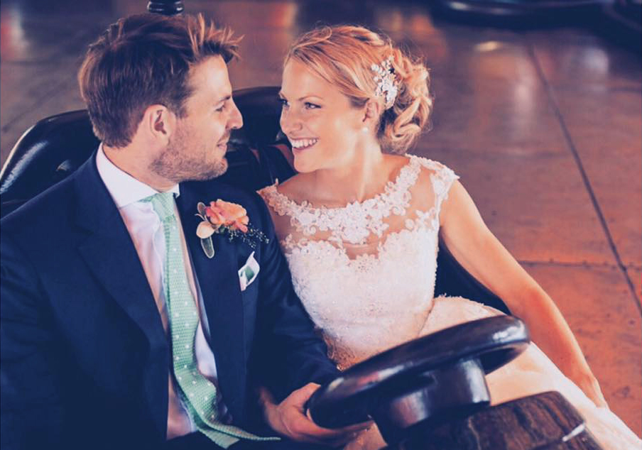 A beautiful bride and groom driving a dodgem car