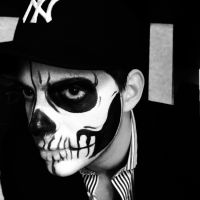Man wearing baseball cap with skull halloween makeup