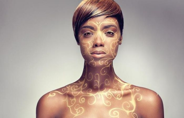 Model bodypainted with gold patterned paint