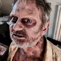 Scary zombie makeup with sunken eyes and rotting skin